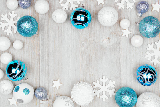 Christmas frame of blue and white decorations. Top view on a grey wood background with copy space.