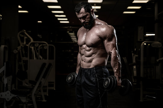 strong bearded male with dumbbells training in sport night gym