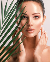 Fototapeta Young beautiful woman with green leaves near body. Skin care beauty treatments concept.  Closeup girl's face with green leaves. obraz