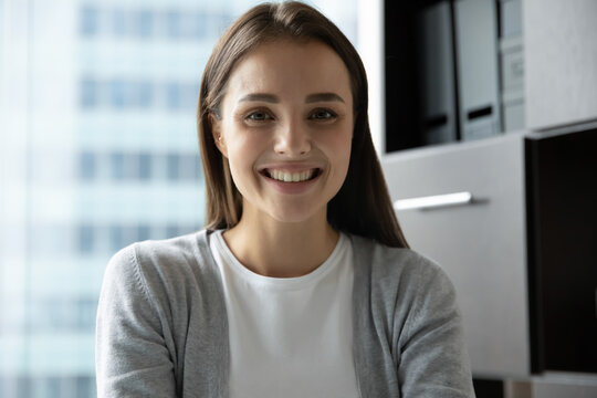 Nice to meet you. Portrait of smiling confident young lady intern trainee employee looking at camera or gadget webcam taking part in video conference online briefing training webinar, profile picture