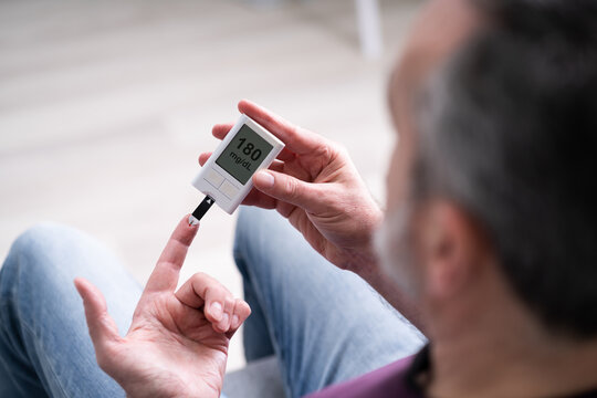 Elderly Man Using Glucometer To Check Blood Sugar Level