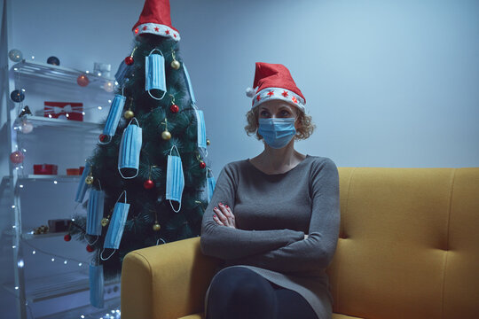 Bored lonely woman sitting at home on Christmas / New Year's eve with medical mask, waiting for guests that will never come.