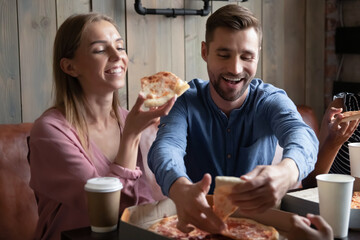 Tastes great. Happy excited young male and female loving couple mates colleagues spending good time at favorite pizzeria with group of friends on weekend having fun enjoying pizza laughing chatting