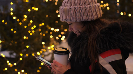 Attractive woman drinking coffee using a mobile phone while walking through the streets on the background of the festive lights of the night city. Glowing blurred bokeh lights of Christmas Fotomurales
