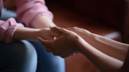 Professional assistance. Close up of biracial female psychologist therapist hands holding palms of...