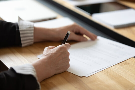Affirming contract. Close up of businesswoman female executive ceo boss sitting at office desk signing order investment agreement insurance policy closing deal confirming paper document approving sale