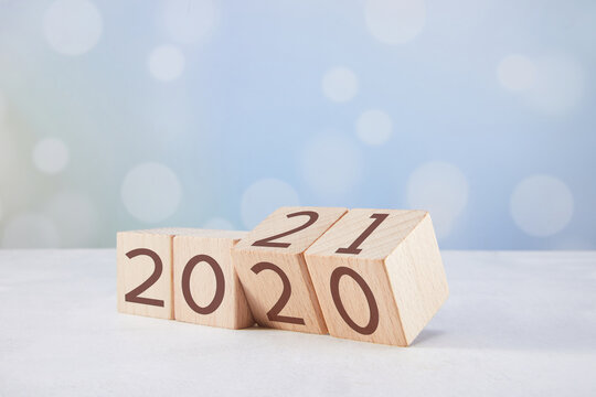 """Closeup of wooden cubes with """"2020"""" numbers changing to """"2021"""""""