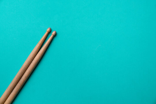 Drum stick on green table background, top view, music concept