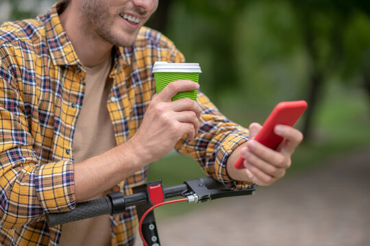 Smiling guy holding a coffee cup and making selfie