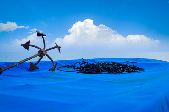 Rusty Anchor & black rope on a fishing boat covered in blue tarpaulin sheet on a beach with blue cloudy sky in the background