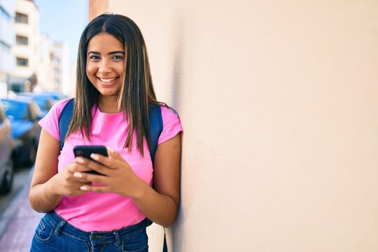Young latin student girl smiling happy using smartphone at university campus.
