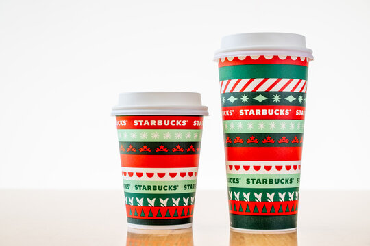 Chiang Mai, Thailand - 07 November 2020 - Two Starbucks coffee take home paper cup in two different sizes, Grande and Tall, sit on a wooden table on November 7, 2020 in Chiang Mai, Thailand