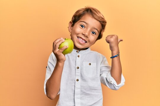 Adorable latin kid holding green apple pointing thumb up to the side smiling happy with open mouth