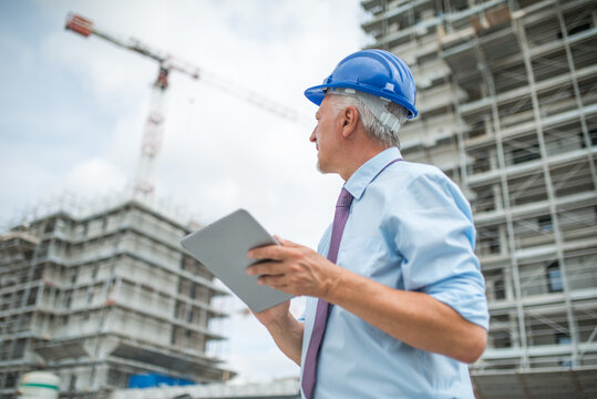 Site manager using his tablet in front of a construction site