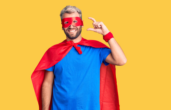 Young blond man wearing super hero custome smiling and confident gesturing with hand doing small size sign with fingers looking and the camera. measure concept.