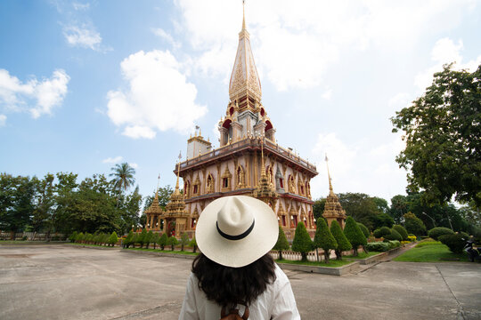 Woman tourist is traveling and sightseeing in Wat Chalong or Chalong Temple is the biggest and most visited temple on Phuket Island, Thailand.