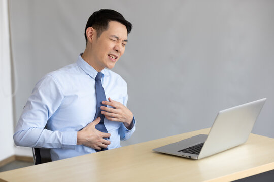 asian businessman suffering from stomachache in office
