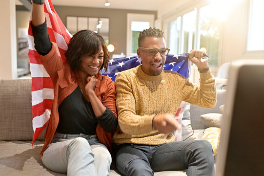 Young african american couple celebrating with US flag, watching TV at home
