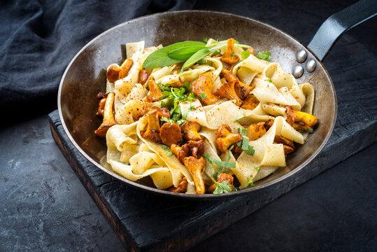 Traditionelle gebratene Tagliatelle con Galletti mit Pilzen angeboten as close-up in einer rustikalen Bratpfanne