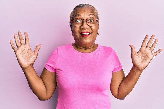 Senior african american woman wearing casual clothes and glasses celebrating mad and crazy for success with arms raised and closed eyes screaming excited. winner concept