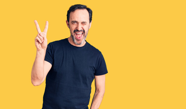 Middle age handsome man wearing casual t-shirt smiling with happy face winking at the camera doing victory sign. number two.
