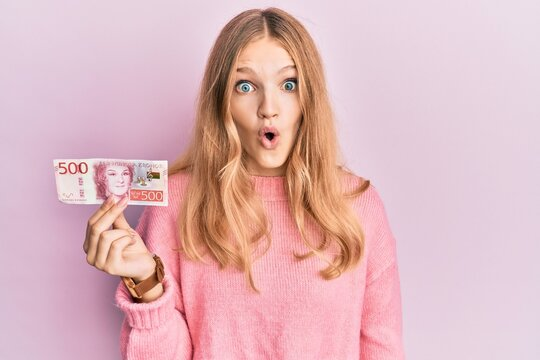 Beautiful young caucasian girl holding 500 swedish krona banknote scared and amazed with open mouth for surprise, disbelief face