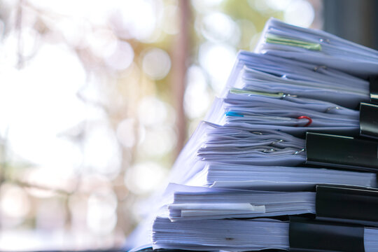 Business paper in offices working for arranging documents unfinished stack of document papers with pen, clip papers on busy office desk, Accounting planning budget concept