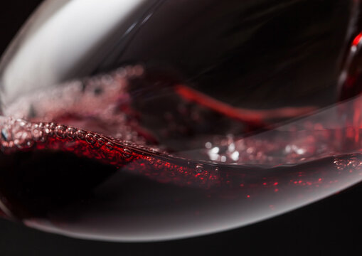 Close up of crystal glass of red wine with bubbles on black.