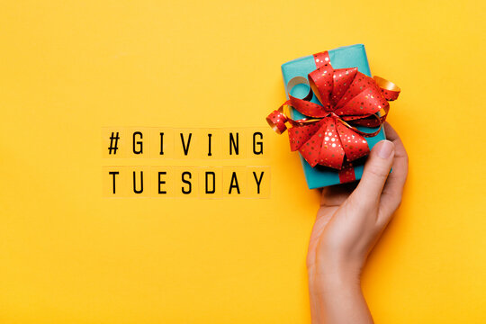 Giving Tuesday. Global day of charitable giving after Black Friday shopping day. Woman hand holding gift box on yellow background