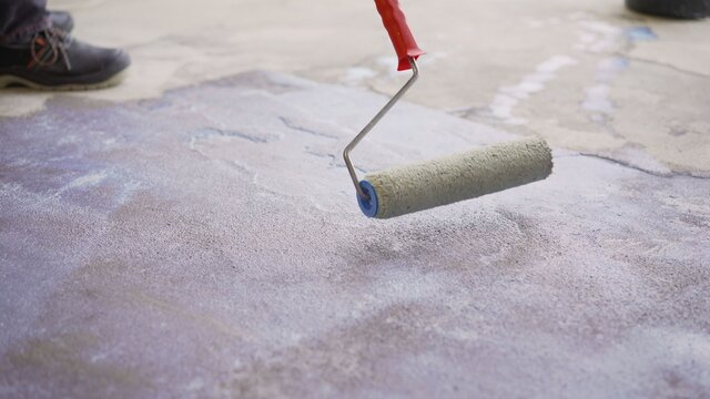 Concrete floor priming is the final preparatory stage for surface strengthening. Priming the concrete floor with a long handle roller. Floor priming process.