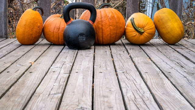 heavy iron kettlebell with a crop of pumpkins on a wooden deck, fall holidays and fitness concept