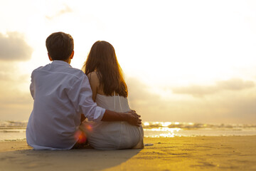 Couple in love watching sunset together on the beach travel summer holidays. People romance concept.