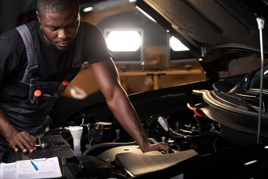 professional car mechanic is examining engine under the hood at auto repair shop, make notes, checking notes in notebook
