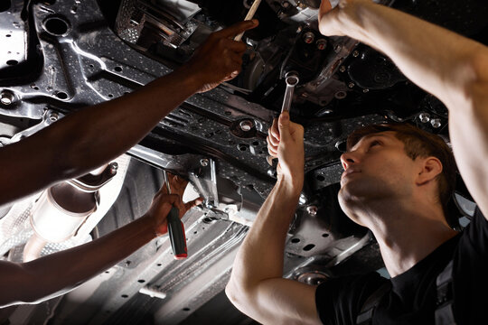 two friendly professional auto mechanic during work, they are successfully repairing car, solve problems together