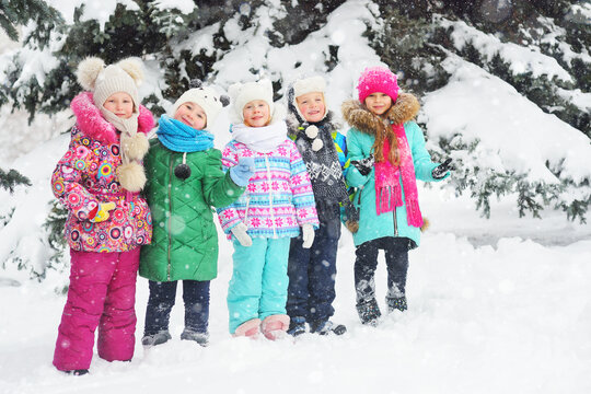 a group of children in colorful bright winter clothes smile against the background of the winter forest and snow. Winter fashion, warm clothes, winter entertainment, Christmas holidays.