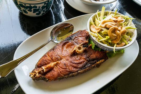 Deep fried king mackerel with spicy mango salad - Thai food.