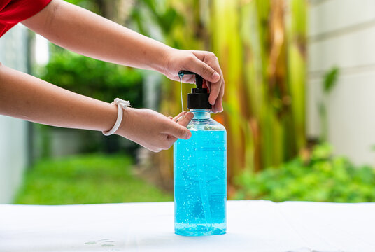 A boy using alcohol hand cleansing gel to clean his hand