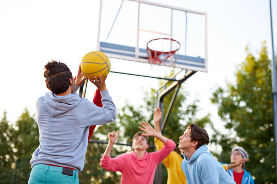 group of young male teenagers in colourful hoodies playing basketball outdoors in the street