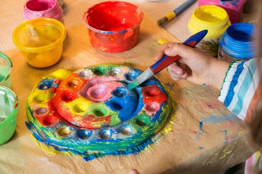 Kind malt mit einem Pinsel einen Salzteig an