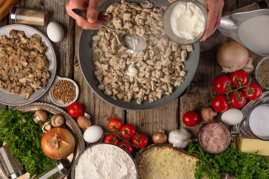 Chef adds sour cream into the pan with frying chicken fillet on variety of ingredients background. Concept of cooking process. Backstage of preparing tasty meal. View from above. Flat lay.