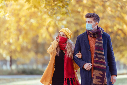 Couple wearing mask walking in autumn park