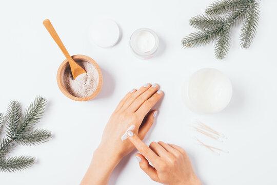 Winter skin care, female hands apply nourishing cream