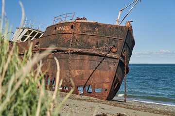 old rusty and rotten ship wreck with holes in its carcass, lying behind long gras on the beach of the coast line of the Strait of Magellan in Patagonia, south America, abandoned places_3