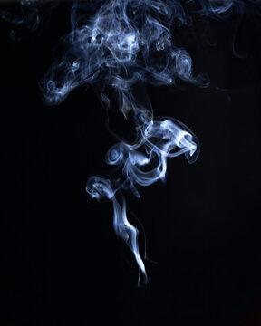 White smoke plume isolated on black background. Ornate ball of smoke
