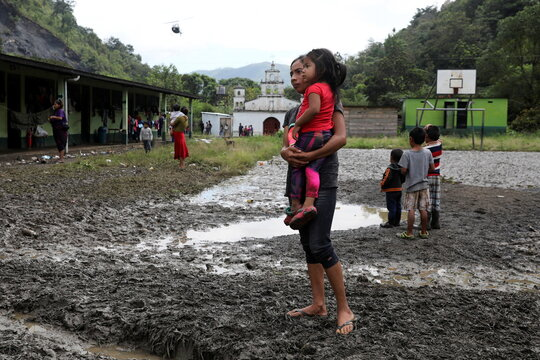 A woman and her daughter wait for goods at a school, being used as a temporary shelter for people from neighboring villages affected from the mudslides caused by heavy rains brought by Storm Eta, in the village of Santa Elena