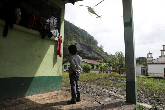 A child observes a helicopter landing at a school, being used as a temporary shelter for people from neighboring villages affected from the mudslides caused by heavy rains brought by Storm Eta, in the village of Santa Elena