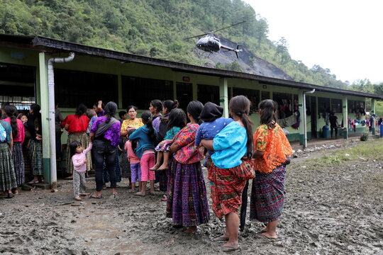 Women observe a helicopter landing at a school, being used as a temporary shelter for people from neighboring villages affected from the mudslides caused by heavy rains brought by Storm Eta, in the village of Santa Elena