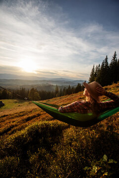 Woman hiker resting after climbing in a hammock at sunset