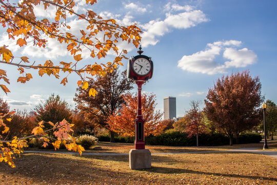Vintage red standing clock in Autumn park with city skyscrapers in the distance and colorful leaves framing - selective focus