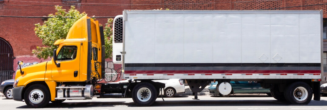 Side view of orange semi cab and trailer parked on urban street. Nobody. Horizontal.